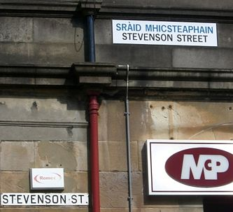 Newer streets signs in parts of western Scotland display names in Scottish Gaelic above English - older signs are in English only. The promotion or proscription of languages is called language planning and is one topic studied in sociolinguistics.
