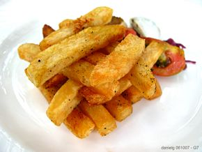 A unique french fry creation served at Antonio's Restaurant in Tagaytay City, Philippines.  These have probably been prepared in drawn butter (butter with all the whey and other liquids removed) after a light coating in seasoning.  Fresh chopped garlic has been added to flavor the fry medium and removed and sprinkled atop the final dish, which can be seen in the photo.  Note the careful arrangement of the fries.
