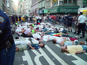 Picture of a street protest scene, with people lying down in a street, surrounded by police, onlookers, and stores in a big city.