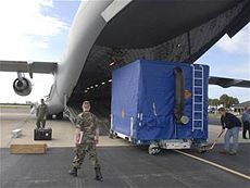 Shipping container being loaded on a USAF cargo plane