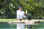 A hotel butler serving drink in Bali.  Note his sarong garb.
