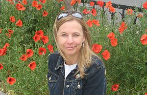 Picture of a woman outdoors smiling with red flowers in the background.