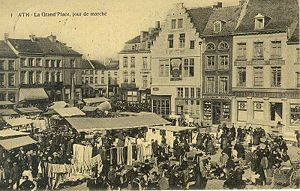 Picture from a postcard of a town square in France in 1900; buildings surround a square where there's a market.