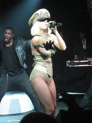 A blond female performs onstage. She is surrounded by male dancers