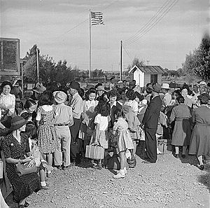 Black and white picture of perhaps 30 people dressed, outdoors, happy, with American flag on pole in background.
