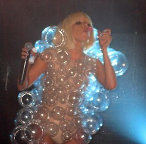 Woman blowing bubbles wearing a costume made of bubbles.