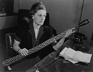 Picture of a woman holding a long cylindrical wiry cable, seated indoors