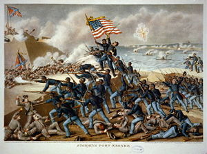 Picture of a battle with many soldiers in blue, on the right, attacking soldiers in gray uniforms in a fort on the left, with an American flag flying, and white smoke throughout.