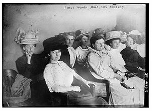 "Picture of seven women wearing different dresses and hats with the words ""First woman jury, Los Angeles"" on the top of this black and white photo."