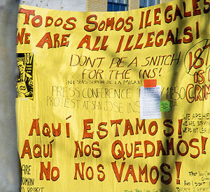 "Picture of a large yellow sign saying ""Todos somos illegales -- we are all illegals"" caption reads Protest against the legal treatment of immigrants in Santa Cruz, California."