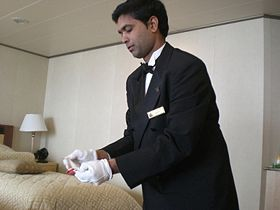 A butler serving vacationers aboard the cruise ship Queen Victoria, 2008.