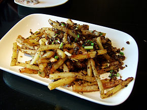 A french fry dish served in Beijing, China.  The potatoes have been fried, tossed in a spicy low-moisture coating, and topped with scallions.